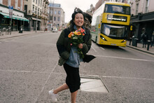 Happy Asian Woman Crossing The Street With Flowers