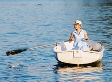 An Elegant Blonde Woman In A Hat Sits On A Boat And Enjoys The Tranquil Lake During Her Summer Vacation.