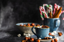 Christmas Candy Canes, A Bowl Of Nuts And A Cup Filled With Miniature Marshmallows