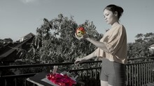 Black And White Slow Motion Footage Of Woman Painter Holding A Pink Dragon Fruit In One Hand And A Paint Brush In The Other. Crazy Conceptual Hyper Realistic Art Performance Outdoors. Modern Artwork.