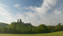 Panning Shot Of Corfe Castle And Surrounding Purbeck Hills In The Early Morning Light.