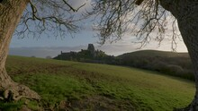 Slow Zoom In Shot Of Corfe Castle Framed By Trees In The Early Morning Light.