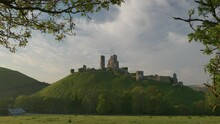 Slow Zoom In Of Corfe Castle Framed By Green Leaves In The Early Morning Light.