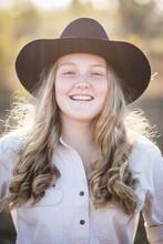 Close Up Of Teenage Girl Wearing Akubra Hat Smiling On Farm In Drought