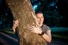 Woman Hand Embracing A Tree In The Forest - Nature Loving, Fight Global Warming, Save Planet Earth