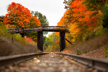 An Old Wooden Bridge Sits Over Railroad Tracks Surrounded By Orange And Yellow Fall Color Trees In Autumn_01