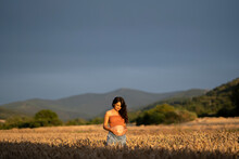 Pregnant Young Woman In Wheat Field During Sunset