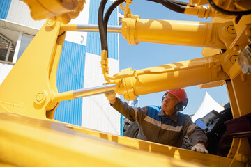 Machinery tractor mechanic checks hydraulic hose system equipment on excavator