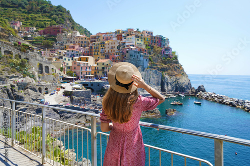 Traveler girl enjoying vacations in Italy. Young woman wearing hat and dress looking at italian village of Manarola with sea.