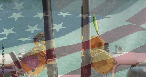 American flag waving against close up view of two fishing rod on a boat