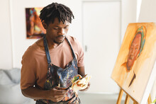 African American Male Painter At Work Painting Portrait On Canvas In Art Studio