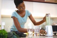 African American Woman In Kitchen Preparing Health Drink