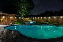 A Backyard Swimming Pool And Jacuzzi Hot Tob At Night