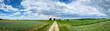 Polna droga wśród upraw rolnych. Obszary wiejskie z uprawami rolnymi w okresie lata.