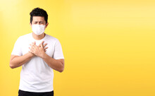 Asian Man Feel Pain On Lung And Wear Protective Mask Pollution Or Transmissible Infectious Diseas And Coronavirus Or Covid-19, Healthcare And Illness Concept.on Yellow Background In Studio For Ads.
