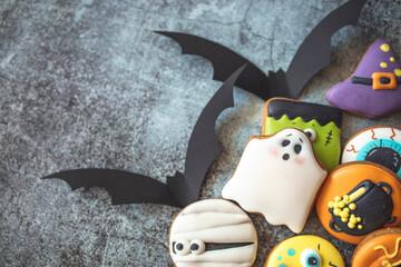 Delicious halloween party cookies. Top view. Halloween Gingerbread Cookies - pumpkin, ghosts, witch hat, spiderweb on halloween background. Top view.
