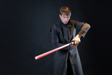A Villain With A Red Lightsaber, A Young Man In A Long Robe Does Fighting Poses,