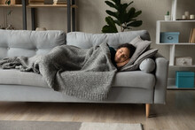 Full Length Peaceful Woman Resting Under Warm Blanket On Cozy Couch In Living Room, Calm Young Female With Closed Eyes Sleeping, Taking Nap Or Daydreaming, Lying On Soft Pillow With Hands Under Cheek