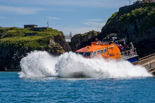 """TENBY, WALES - JUNE 15 2021: The RNLI Tamar Class Offshore Lifeboat """"Haydn Miller"""" Launches From The Slipway At The Lifeboat Station In The Resort Town Of Tenby, Pembrokeshire, Wales"""