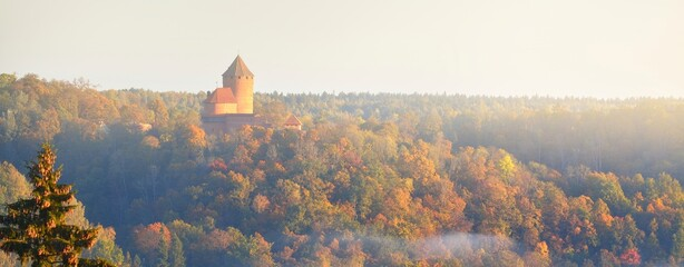 Close-up of the Turaida castle tower and golden forest in a clouds of morning fog at sunrise. Travel guide, sightseeing theme. Gauja national park, Latvia