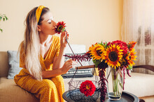 Woman Smells Sunflower Arranging Bouquet With Zinnia Flowers In Vase At Home. Lady Enjoys Fresh Blooms. Interior
