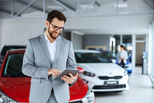 Smiling, Friendly Car Seller Standing In Car Salon And Using Tablet To Check On New Messages Customers Post On Internet.