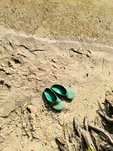 A Pair Of Abandoned Flip Flops In The Sand At A Lake