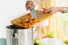 Woman Putting Carrot Peels Into Compost Bin
