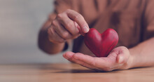 Male Hands Holding Red Heart, World Mental Health Day And World Heart Day, Life And Health Insurance, CSR Social Responsibility, Organ Donation, concept Of Love