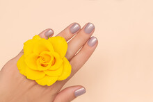 Female Hand With Pale Purple Nail Design. Female Hand With Yellow Rose Ring. Woman Hand On Light Orange Background