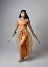Full Length Portrait Of Pretty Young Asian Woman Wearing Golden Arabian Robes Like A Genie, Holding A Sword Weapon, Isolated On Studio Background.