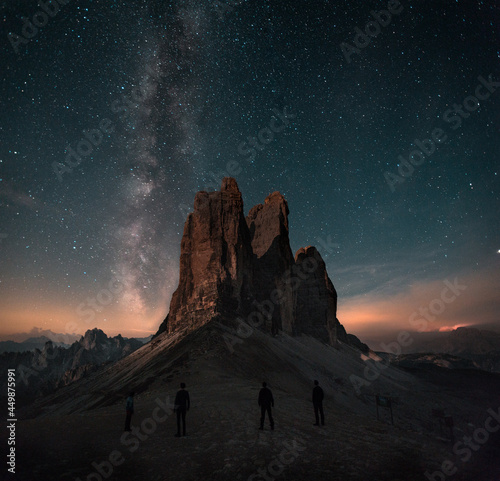 Boy, man is standing in front of moutains Tre Cime di Lavaredo in Dolomites, Italy during night with full of stars and Milky way. Amazing landscape night photo with atmosphere.