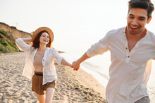 Excited Smiling Young Couple Two Friends Family Man Woman In White Clothes Hold Hands Running Walk Stroll Dance Together At Sunrise Over Sea Beach Ocean Outdoor Seaside In Summer Day Sunset Evening.