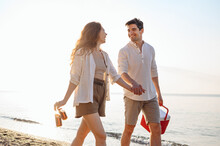 Young Couple Friend Family Man Woman 20s In White Clothes Drink Beer Hold Picnic Bag Refrigerator Hold Hands Walk Rest Together At Sunrise Over Sea Beach Outdoor Seaside In Summer Day Sunset Evening