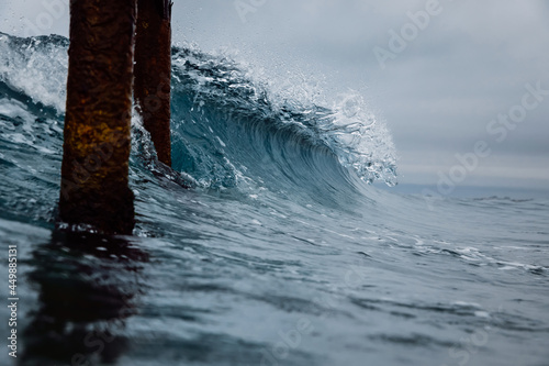 Crashing glassy wave on the beach. Breaking ocean wave and pier