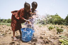 Two Playful Little African Sisters Irrigating Their Father's Cabbage Field, With Eyes Closed And A Wide Smile On Their Faces