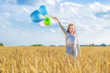 Happy Young Girl With Red Hair Stands With Balloons In Her Hand Among Wheat Field Against Blue Sky