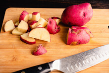 Chopping Red Potatoes In A Bamboo Cutting Board: Cutting Red Potatoes Into Bite Size Pieces On A Wooden Cutting Board
