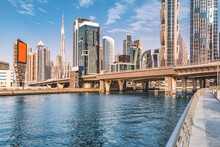 Scenic View Of High Skyscrapers With Offices, Hotels And Residential Buildings In UAE. Road Over The Bridge And Flyover Passes Through The Dubai Creek Canal