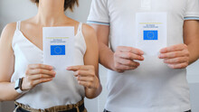 Unrecognized Vaccinated Couple Of Man And Woman Showing Real Paper EU Digital COVID Certificate. Coronavirus Vaccination Advertisement Campaign. Vaccine Done