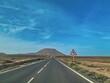 Road Leading Towards Mountain Against Blue Sky