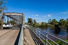 Brown Floodwaters Rising Under Bridge With Pedestrian Crossing Footparh