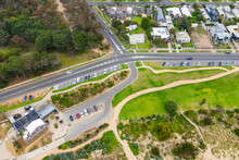 Aerial View Of Coastal Road Along Side A Grassy Reserve, Carpark And Housing
