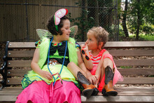 Two Young Girls Wearing Bright Dress-up Sitting On A Park Bench