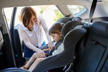 Mum Putting Daughter In Child Car Seat