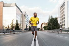 African American Sportsman Jogging On Middle Of The Street In The City Outdoors