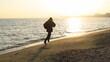 Człowiek biegnący po plaże zimą przy wschodzie słońca, Sopot, Polska