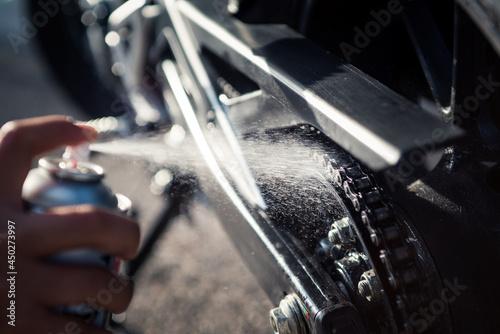 Szczegół ręcznego nakładania smaru w sprayu na łańcuch motocyklowy. Close-up zdjęcie kropelek oleju rozpryskiwania.