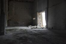 Abandoned Industrial Interior. Dark Empty Warehouse With Cracked Concrete Walls, Broken Bricks And Light Falling Through Open Door