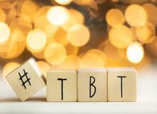 Hashtag TBT Throwback Thursday Written With Wooden Cubes With Shiny Bokeh Background, Social Media Concept